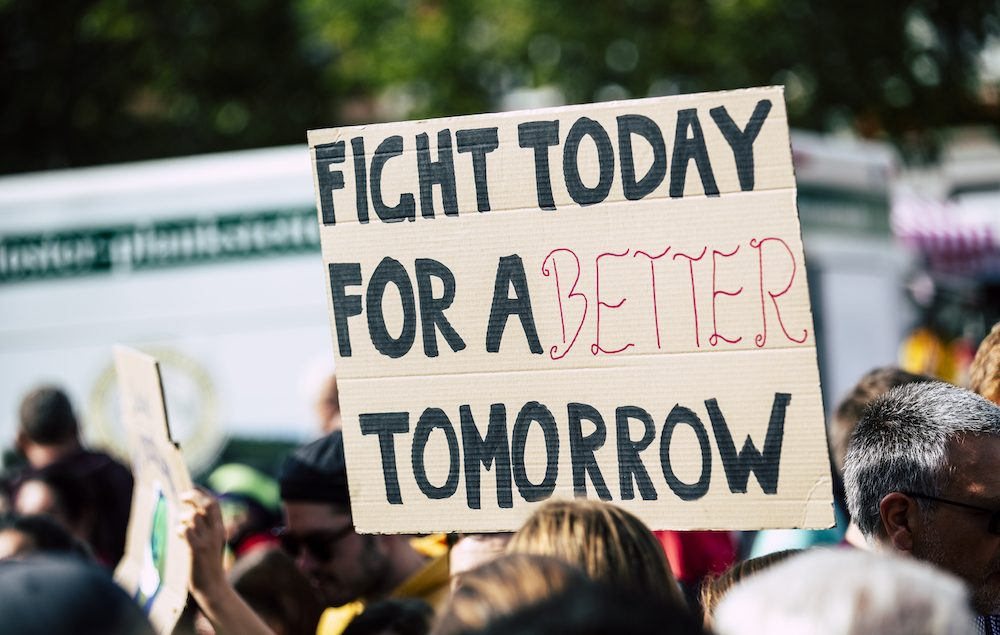 Protester holding a fight for a better tomorrow sign