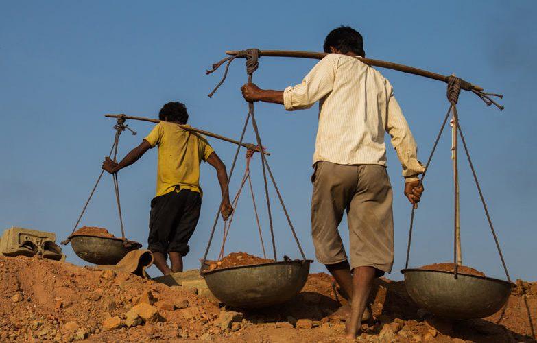 Child labourers carrying broken bricks in India.
