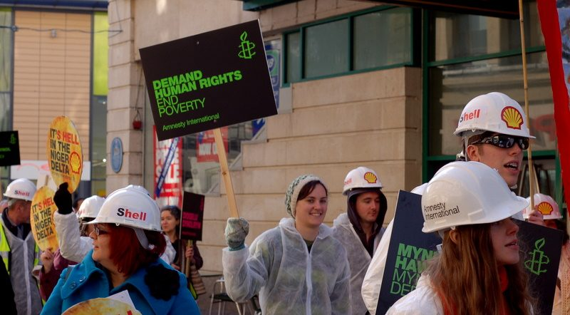 Poeple at a protest against company Shell wear hard hats and hold placards