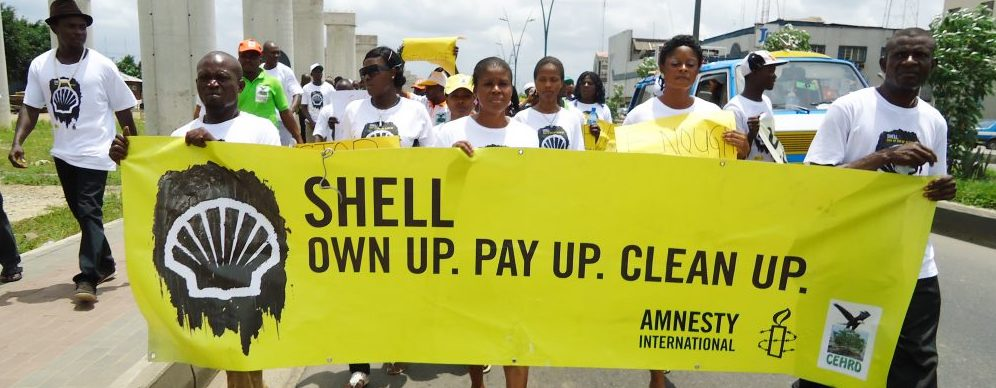 Activists in Nigeria carry a banner to protest against Shell
